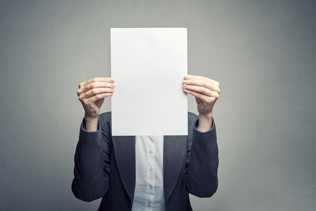 Anónimo mujer que cubre la cara con una hoja de papel