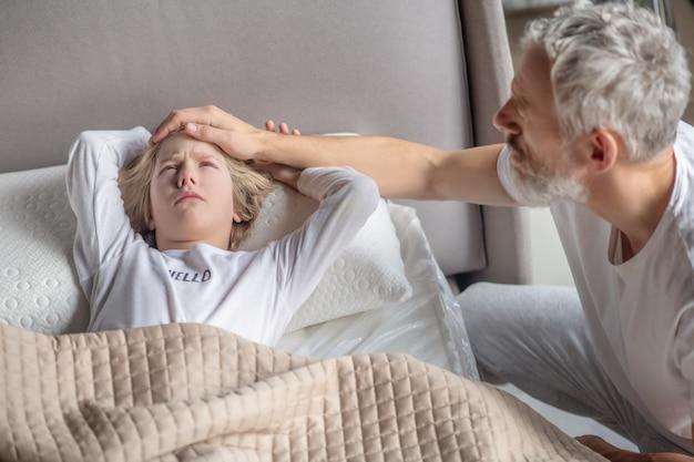 Ansiedad. papá cariñoso mostrando ansiedad poniendo su mano sobre la frente del niño que se despierta en la cama