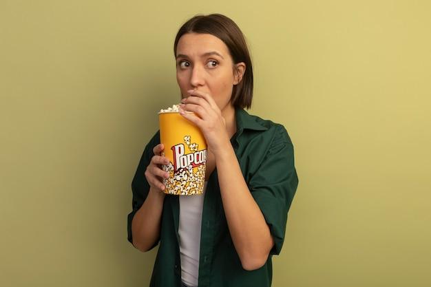 Ansiosa mujer bastante caucásica come y sostiene un cubo de palomitas de maíz mirando al lado en verde oliva
