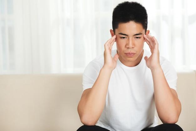 Ansioso joven asiático sentado en el sofá en casa y frotando sus sienes