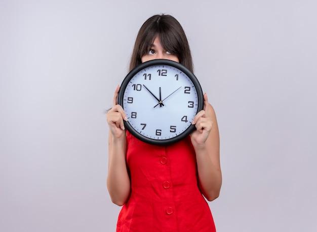 Ansioso joven caucásica sosteniendo el reloj con ambas manos y mirando hacia arriba sobre fondo blanco aislado con espacio de copia