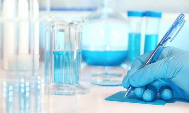 Antecedentes científicos o médicos con vidrio microscópico deslizante de mano enguantada