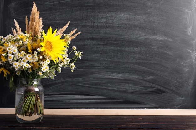 Antecedentes del día del maestro. tablero de tiza negra copia espacio vacío y flores silvestres frescas en florero.