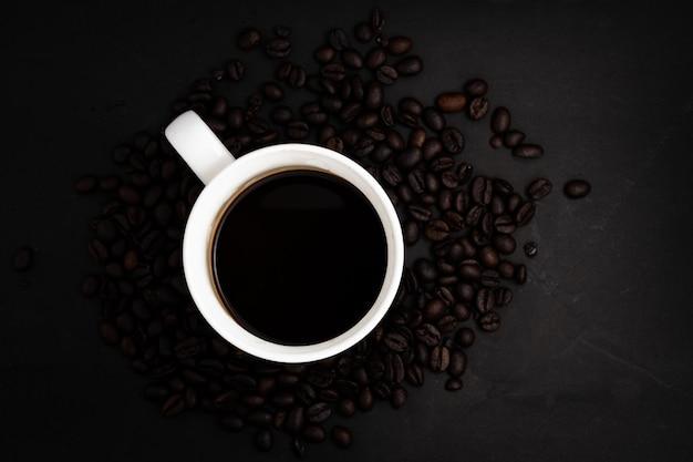 Antecedentes de los granos de café y una taza de café, la vista superior