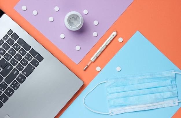 Antecedentes médicos. espacio de trabajo del médico moderno. ordenador portátil, pastillas, máscara de gasa, termómetro sobre fondo de color pastel.
