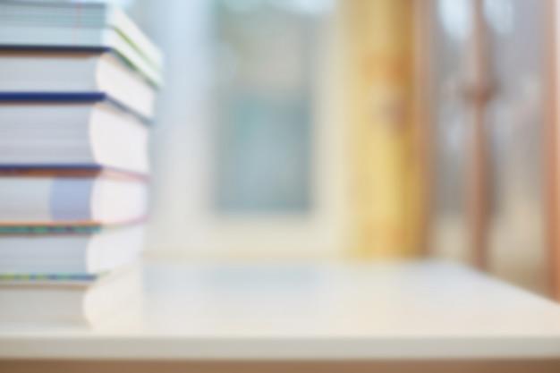 Antecedentes sobre el tema de formación, educación. escritorio con libros, estantería y ventana desenfocada. concepto de escuela o tarjeta de felicitación con el inicio del aprendizaje.