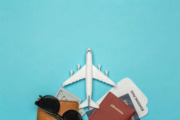 Antecedentes de viaje artículos para viajar y vuelos: boletos, pasaporte, dinero, gafas de sol sobre un fondo de color. concepto de descanso y vacaciones.