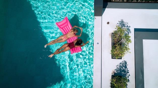 Antena dos mujeres jóvenes alegres que disfrutan en flotadores inflables charlando en la piscina