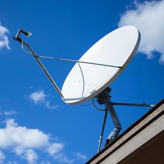 Antena parabólica blanca con cielo azul