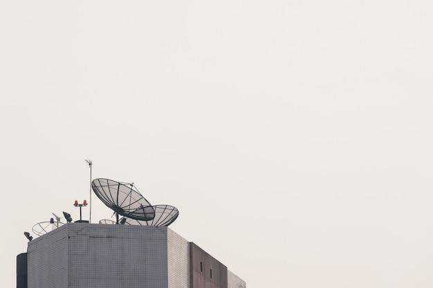 Antena parabólica en edificio de gran altura con cielo claro de puesta de sol en el fondo