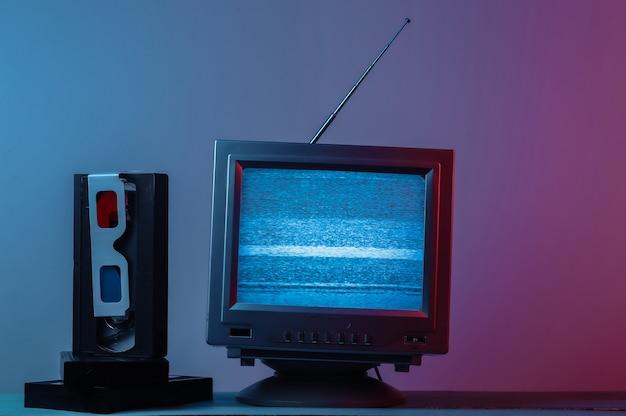 Antena, receptor de tv anticuado con cassette de video de gafas estéreo anaglifo en luz de neón degradado azul rosa retro entretenimiento de los medios de comunicación de los años 80