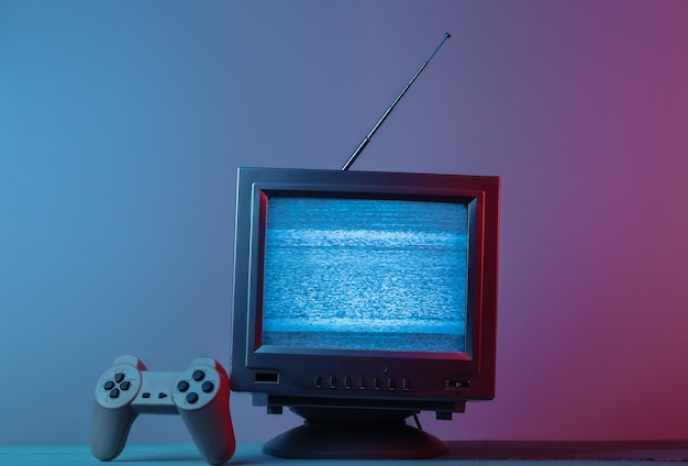 Antena receptor de tv antiguo con gamepad en luz de neón degradado azul rosa retro media entertainment 80s retro wave