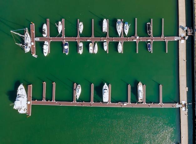 Antena sobre el pequeño puerto deportivo en una cuenca del muelle en el pequeño puerto, vista aérea famoso destino turístico de vacaciones de verano