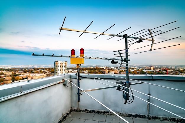 Antena de tv en el techo de un edificio de varios pisos.