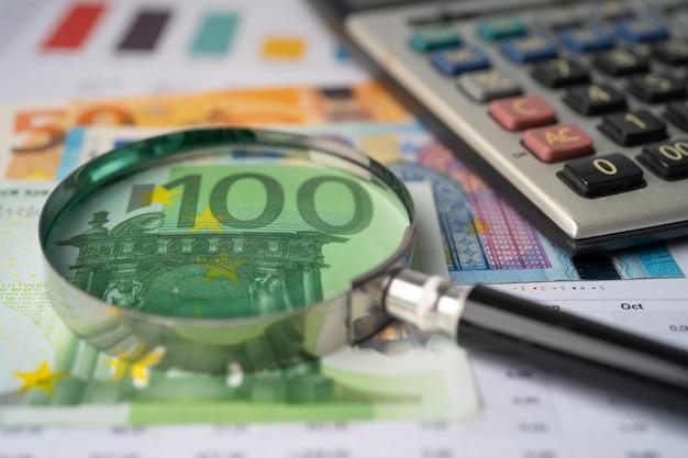 Anteojos con calculadora en billetes en euros y fondo de papel cuadriculado