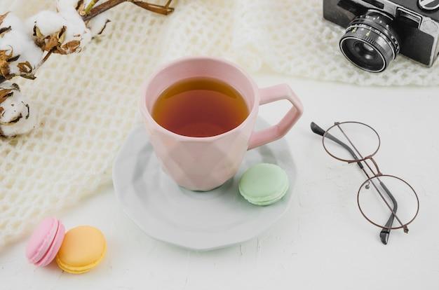 Los anteojos; cámara; ramita de algodón con taza de té de hierbas y macarrones sobre fondo blanco