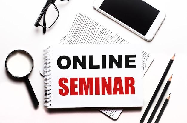 Anteojos, lupa, lápices, un teléfono inteligente y un cuaderno con el texto seminario en línea
