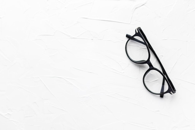 Anteojos con marco negro sobre fondo blanco. los anteojos. gafas redondas con lentes transparentes. cerrar anteojos con técnica borrosa. accesorio de moda. tema de oftalmología. endecha plana.