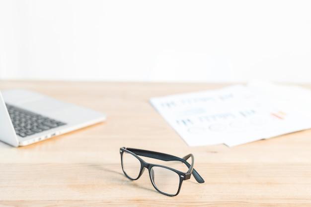 Anteojos negros frente a una computadora portátil y gráfico en un escritorio de madera