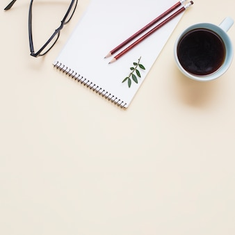 Anteojos negros; taza de té y dos lápices en la libreta espiral contra el telón de fondo beige