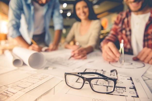 Anteojos sobre borradores, jóvenes arquitectos diseñadores trabajo en equipo