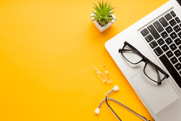 Anteojos sobre laptop con ampolla; estetoscopio con planta suculenta sobre fondo amarillo