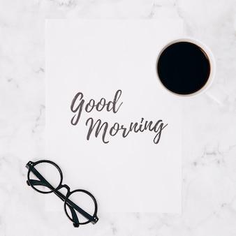 Anteojos y taza de café sobre el texto de buena mañana en papel sobre fondo blanco con textura de mármol