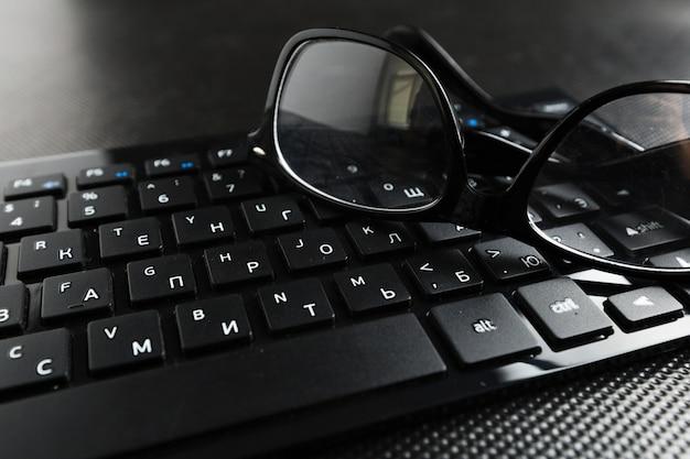 Anteojos y teclado sobre la mesa