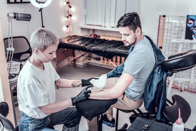 Antes de hacer un tatuaje. maestro de tatuaje femenino profesional rociar alcohol en la mano desnuda secándolo
