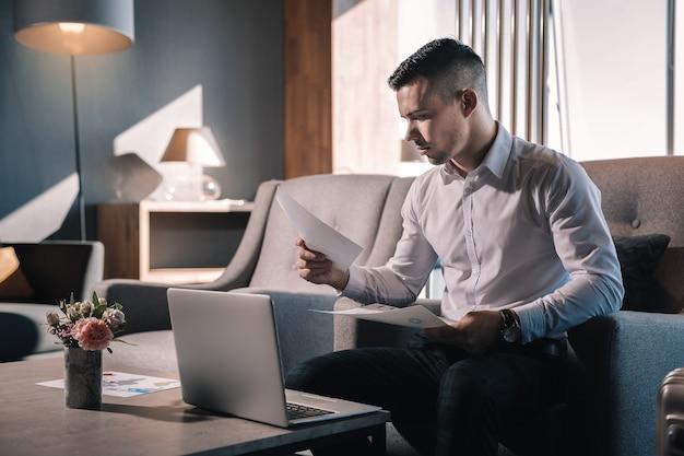 Antes de la reunion. joven apuesto director financiero inteligente mirando documentos antes de una reunión importante