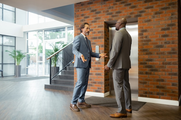 Antes de la reunión oficial. empresario de pelo gris hablando con su socio antes de la reunión oficial
