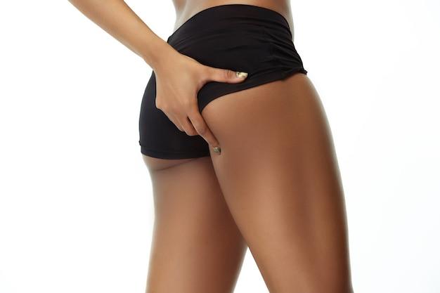 Anticelulitis. cuerpo de mujer bronceada delgada aislado sobre fondo blanco de estudio. modelo de mujer afroamericana con forma y piel bien cuidadas. belleza, cuidado personal, pérdida de peso, fitness, concepto de adelgazamiento.