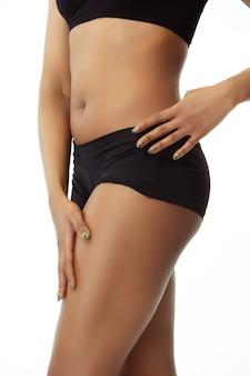 Anticelulitis y depilación. cuerpo de mujer bronceada delgada sobre fondo blanco de estudio. modelo afroamericano de cuidada forma y piel. belleza, cuidado personal, pérdida de peso, fitness, concepto de adelgazamiento.