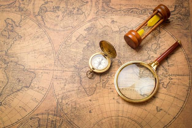 Antigua brújula, lupa y reloj de arena en mapa vintage