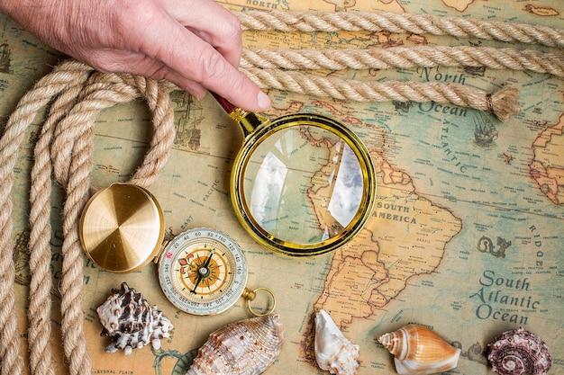 Antigua brújula retro vintage, lupa en el mapa del mundo antiguo