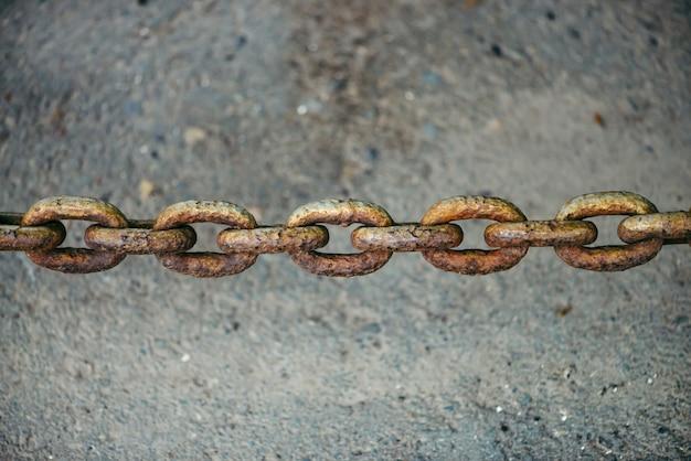 Antigua cadena oxidada oxidada colgando sobre el asfalto de cerca con espacio de copia