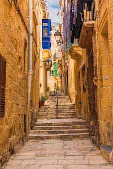 Antigua callejuela medieval con edificios amarillos con coloridos balcones en la ciudad de singlea, valletta, malta