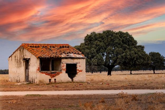 Antigua casa dañada con un hermoso cielo naranja durante la puesta de sol
