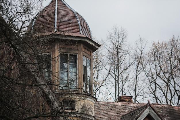 Antigua casa gótica abandonada. la mansión en ruinas se encuentra en el parque. ventana misteriosa fondo gótico lugar de fiesta de halloween. casa de miedo ventana y techo del antiguo palacio. aterrador edificio medieval