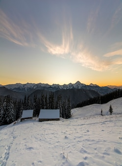 Antigua casa de madera, cabaña y granero en nieve profunda en el valle de la montaña, bosque de abetos, colinas arboladas en el cielo azul claro al amanecer copia espacio de fondo paisaje de montaña invierno panorama.