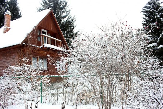 Antigua casa de madera rústica en el bosque nevado en invierno