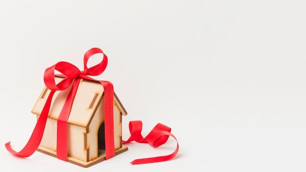 Antigua casa en miniatura con cinta roja sobre papel pintado blanco