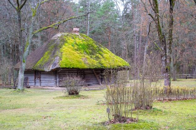 Antigua casa de troncos de madera. ver con ventana, puerta de entrada y con musgo en el techo.