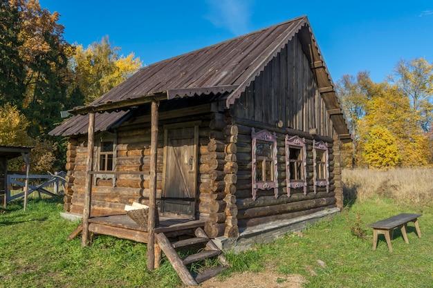 Antigua casa de troncos en el pueblo ruso. banco en el patio.