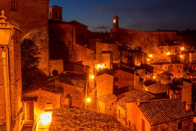 Antigua ciudad italiana de sorano en la noche. las luces de la calle iluminan los techos de las casas antiguas