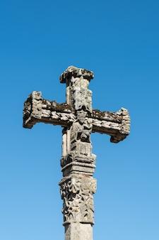 Antigua cruz de piedra tallada con la virgen maría sosteniendo al niño jesús en sus brazos. copia espacio