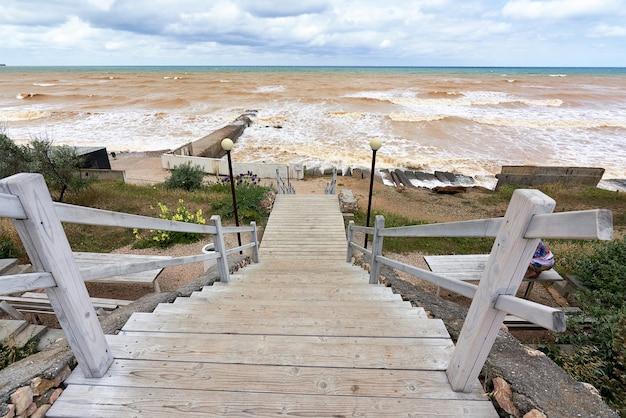 Una antigua escalera de madera con barandillas que conducen a la playa del mar olas en un mar desierto