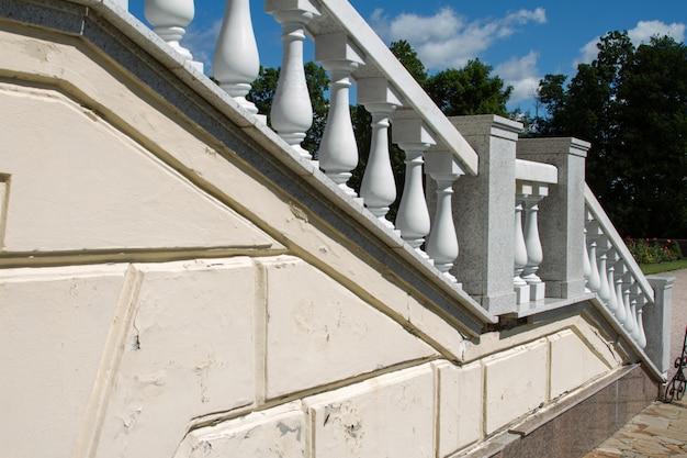 Antigua escalera de piedra blanca con balaustres clásicos