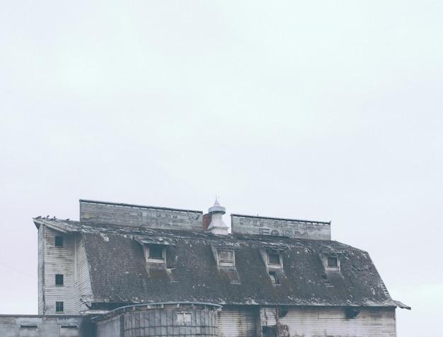 Antigua granja abandonada con un nombre de empresa sucio apenas visible en el techo
