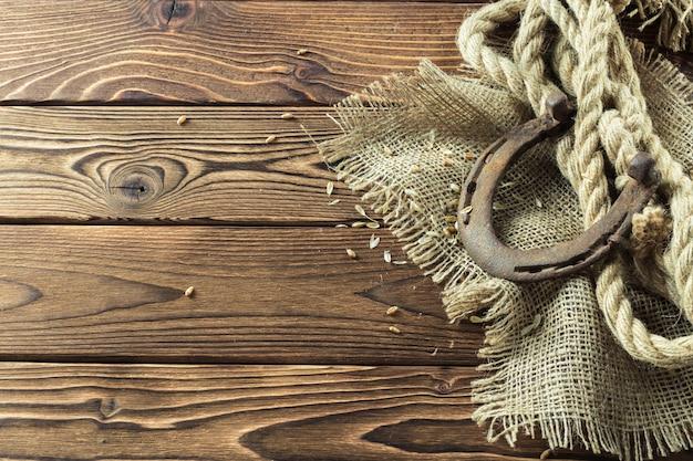 Antigua herradura y cuerda sobre fondo de madera